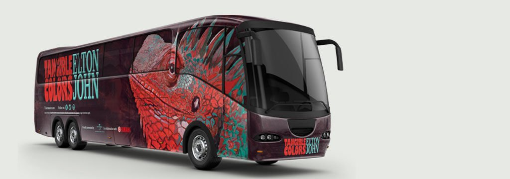 Tour bus with the Green Lizard in red and green illustrated on the side of the bus.
